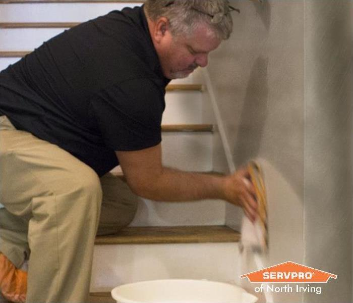 man in a black shirt, khaki pants, and orange shoe covers cleans a soot damaged wall
