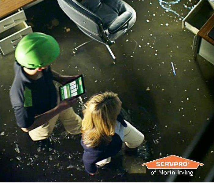 man and woman walking through a flood office