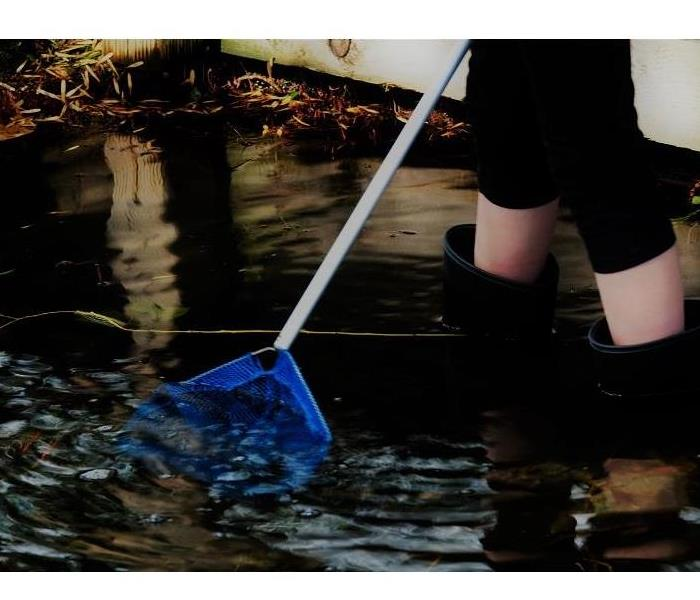 woman in black rain boots using blue pool net skimmer in water damage